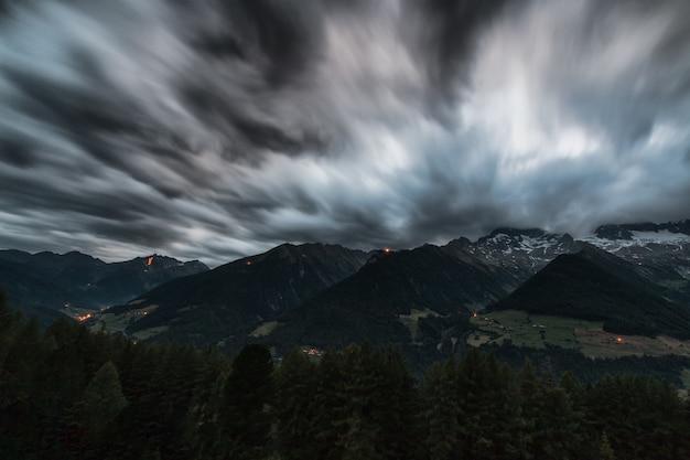 Lapso de tiempo pinos cerca de montañas bajo nubes grises