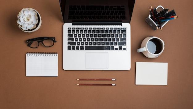 Una laptop abierta; con taza de café; papel; lapices anteojos y libreta sobre fondo de papel marrón