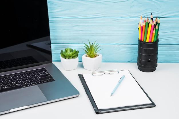 Laptop alta vista con accesorios de oficina.