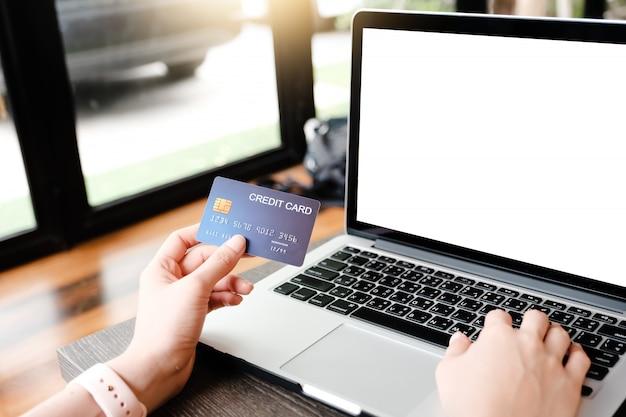 Laptop en blanco y pagando dinero con tarjeta de crédito