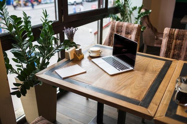 Laptop con bloc de notas en cafe en mesa
