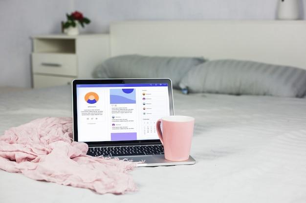 Laptop en cama con taza de café rosa
