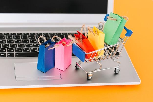 Laptop con carrito de compras y paquetes de juguetes.