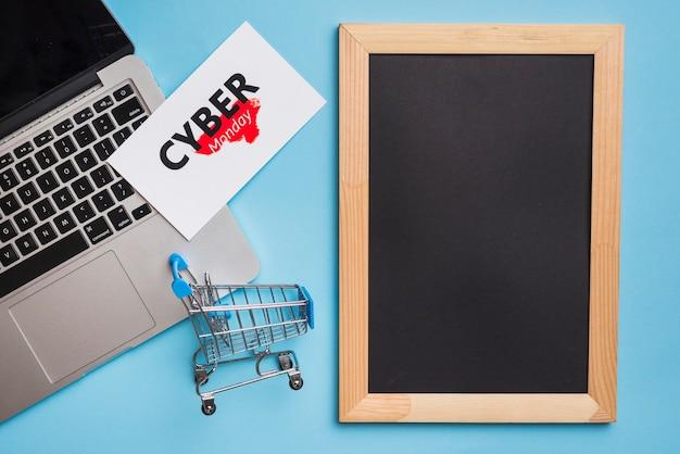 Laptop cerca de la etiqueta con título de cyber monday y marco de fotos