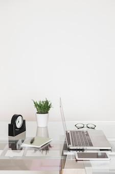 Laptop cerca de smartphone y reloj en mesa