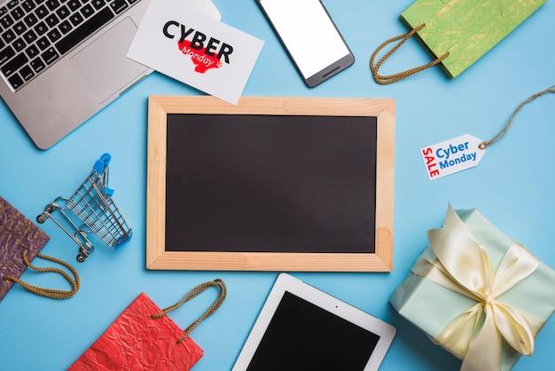 Laptop cerca de smartphone, tags y marco de fotos.