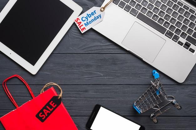 Laptop cerca de smartphone, tags, tablet y paquete.