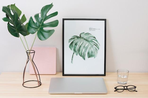 Laptop con foto y vasos en mesa