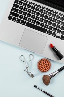Laptop y herramientas profesionales de maquillaje sobre fondo azul claro