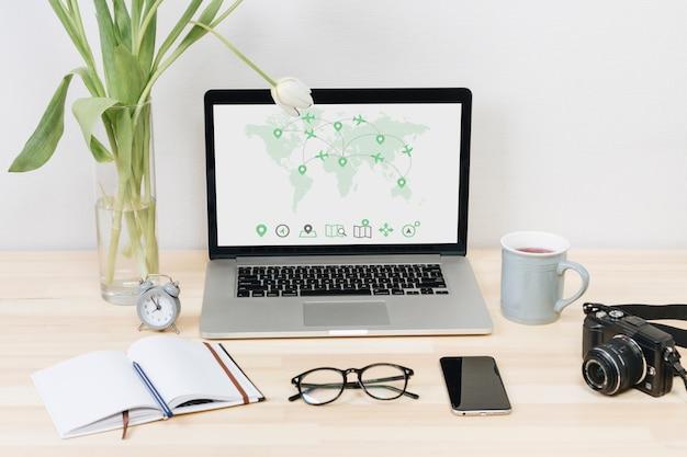 Laptop con mapamundi en pantalla sobre mesa
