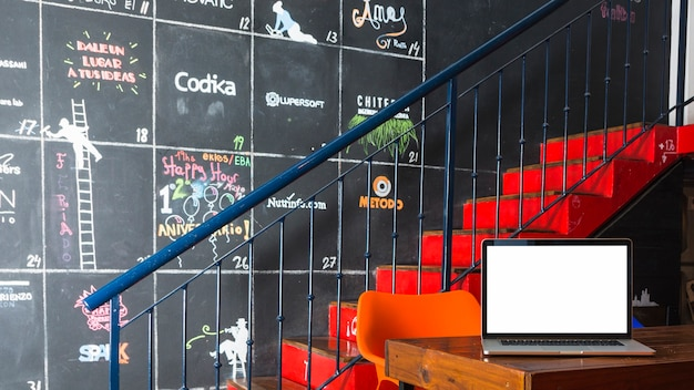 Laptop en mesa frente a escalera y pared decorativa