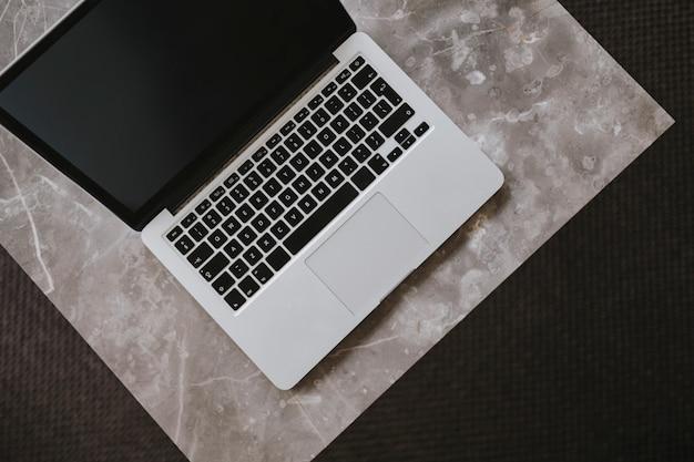 Una laptop en una mesa de mármol.