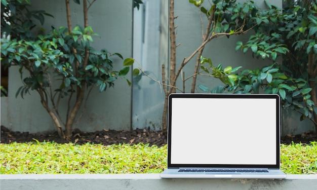 Laptop con pantalla blanca en blanco frente a plantas
