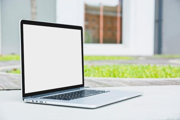 Laptop con pantalla blanca en blanco en pasarela