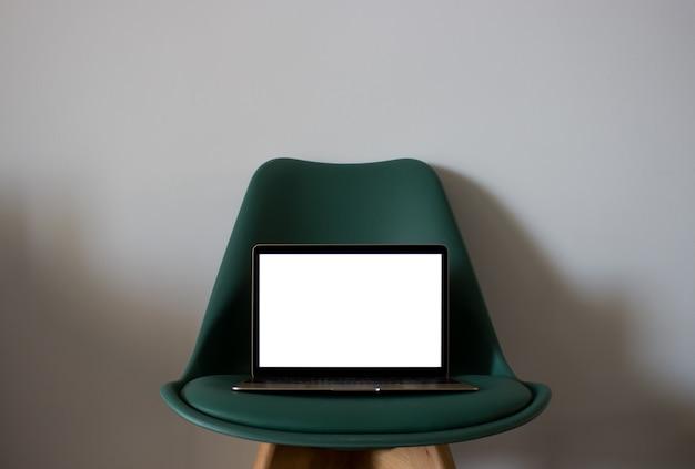 Laptop con pantalla en blanco en silla