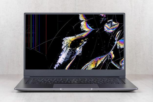Laptop con una pantalla rota en manchas de color y grietas