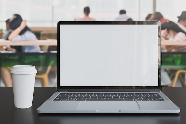 Laptop pantalla vacía colocada con una taza de café con leche en la mesa en el espacio de trabajo conjunto