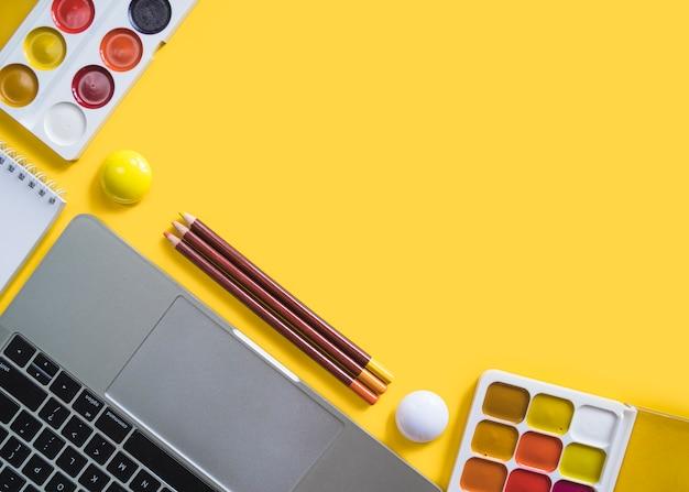Laptop y pinturas sobre superficie amarilla.
