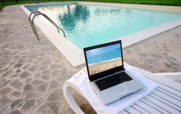 Laptop con salvapantallas en la playa a lo largo de una piscina.