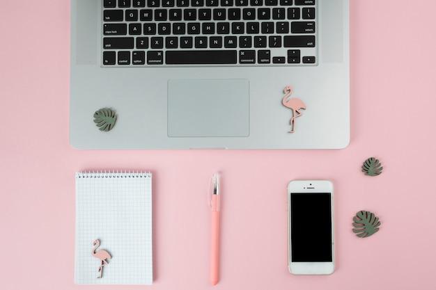 Laptop con smartphone y pequeños flamencos.