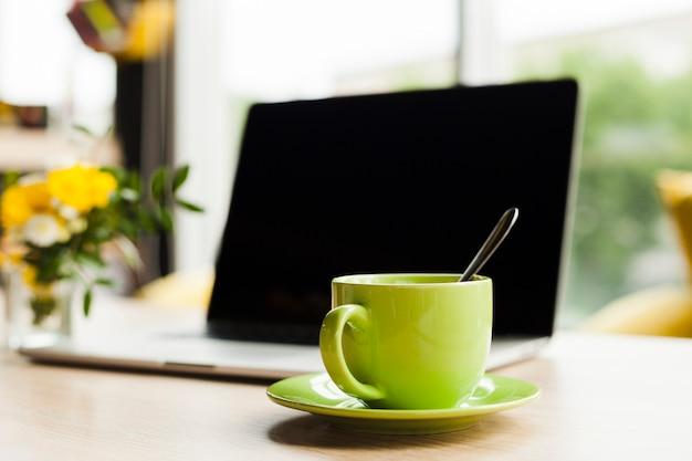 Laptop y taza de café de cerámica verde en la mesa de trabajo