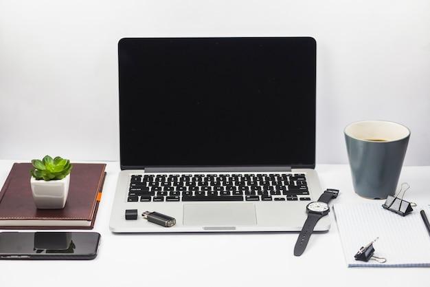 Laptop con taza de café y planta