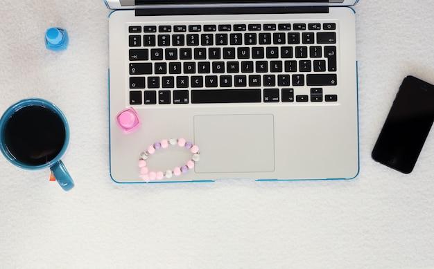 Laptop, teléfono inteligente, taza y esmalte de uñas
