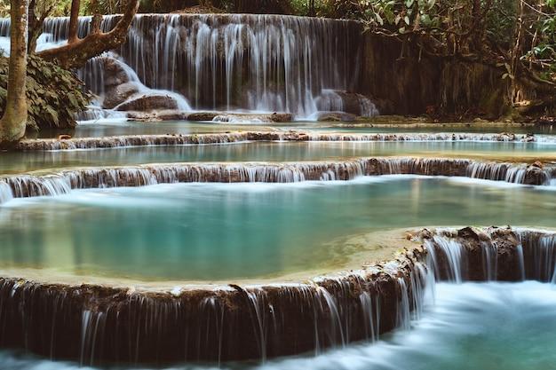 Larga exposición de la hermosa cascada tropical kuang si en luang prabang, laos