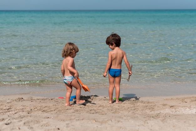 Larga vista de niños de pie en la playa con juguetes.