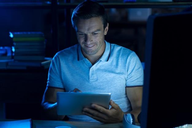 Largas horas. hombre trabajador diligente brillante sentado en la oficina