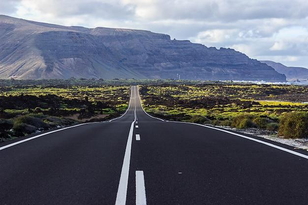 Largo camino hacia las montañas con el mar al lado