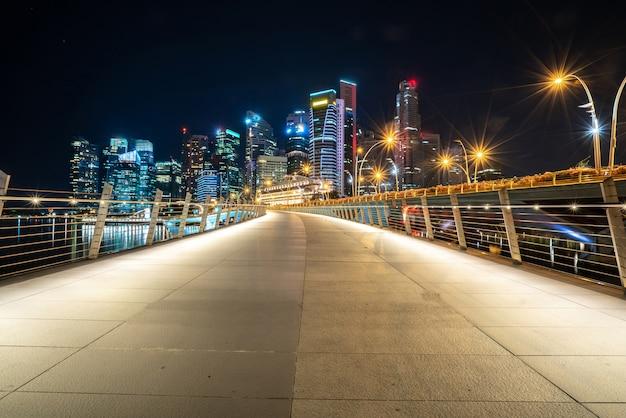 Largo camino con rascacielos en la noche