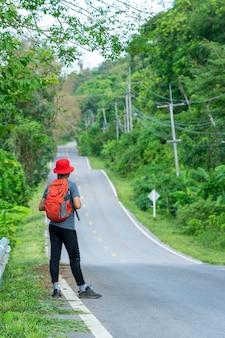 Largo camino por recorrer, turista de pie en la carretera, concepto de viaje, desafío del viaje.