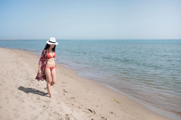 Largo de mujer caminando en la playa.