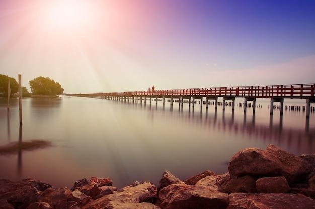Largo puente rojo luz del sol cielo árbol en playa mar
