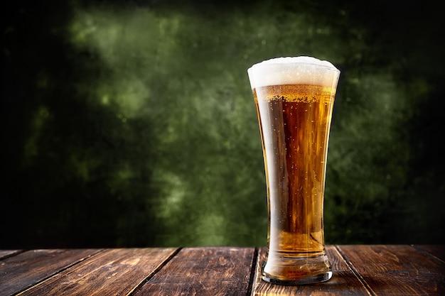 Largo vaso de cerveza sobre fondo verde oscuro