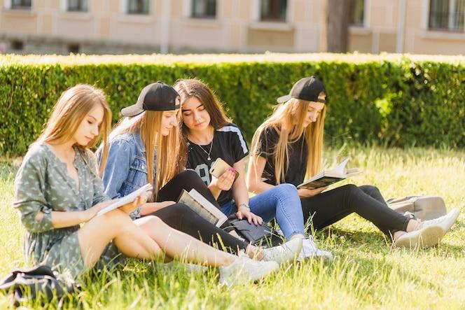 Las adolescentes hablando cerca de amigos de lectura