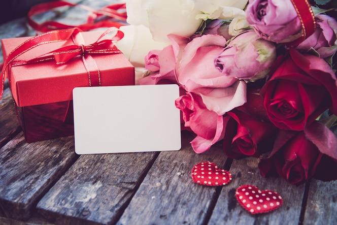 Las cajas de regalo rojas, los corazones rojos y las rosas se colocan en un piso de madera.
