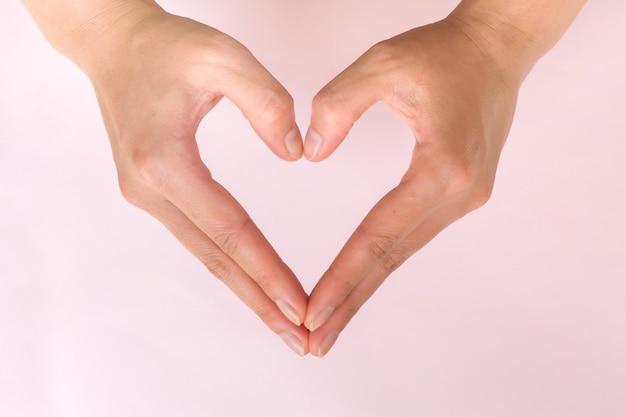 Las manos de mujer hacen forma de corazón sobre fondo rosa. simbólico del amor. tema de san valentín