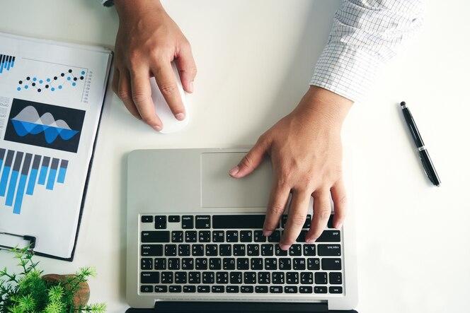 Las manos del hombre usando la computadora portátil