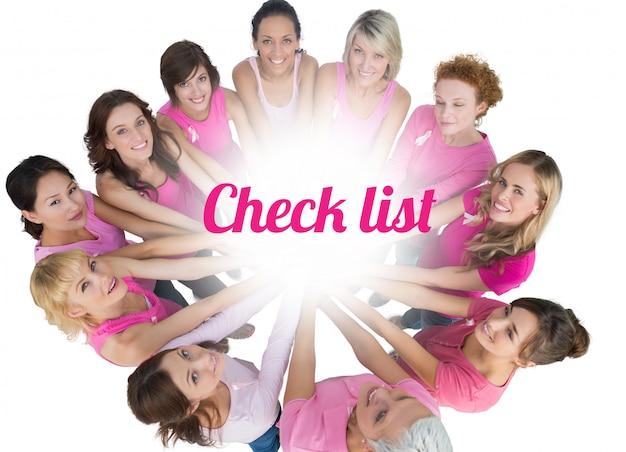 Las mujeres alegres se unieron en un círculo y levantando la vista para ver el rosa rosado del cáncer de mama