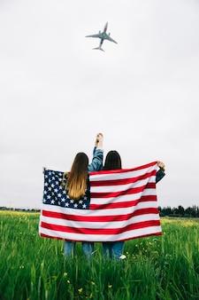 Las mujeres con bandera estadounidense se quedan en el campo