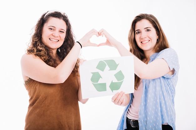 Las mujeres felices que sostienen reciclan la pancarta que hace la muestra del corazón con las manos