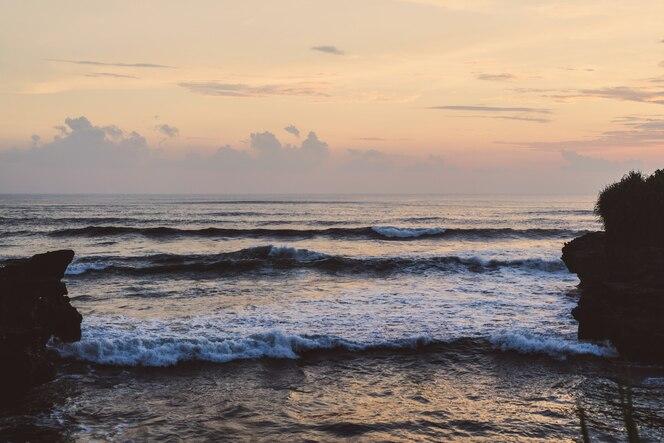 Las olas del océano se están rompiendo contra las rocas. salpicaduras de las olas del océano al atardecer.