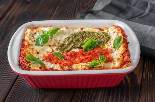 Lasaña cubierta con salsa de tomate y pesto en un molde para hornear