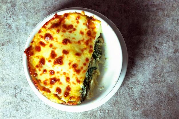 Lasaña de espinacas con queso en plato blanco
