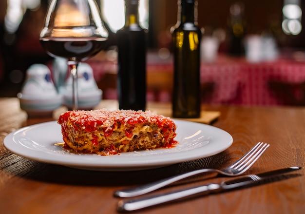 Lasaña italiana adornada con salsa de tomate y parmesano rallado servido con vino tinto