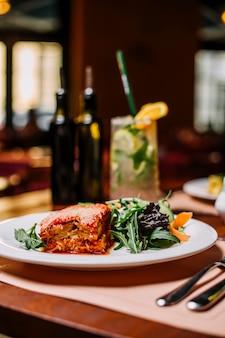 Lasaña italiana servida con ensalada de rúcula