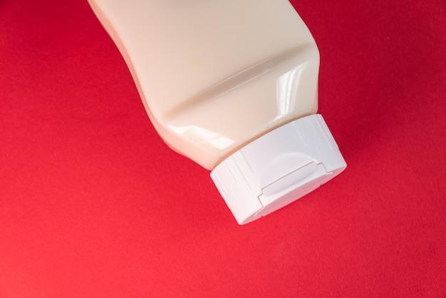 Lata de mayonesa sobre fondo rojo.