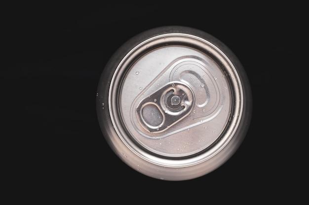 Lata de refresco de metal con gotas de agua. vista superior de una lata de aluminio cerveza. contenedor metálico de bebidas, bebidas. superficie redonda de acero.